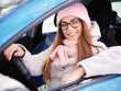Young adorable blonde woman in pink knitted hat scarf car driver hands on wheel winter outdoors.