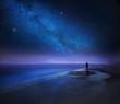 Leinwanddruck Bild - Starry night sky over sea and beach with man silhouette
