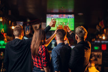Friends Watches Football On TV In A Sport Bar