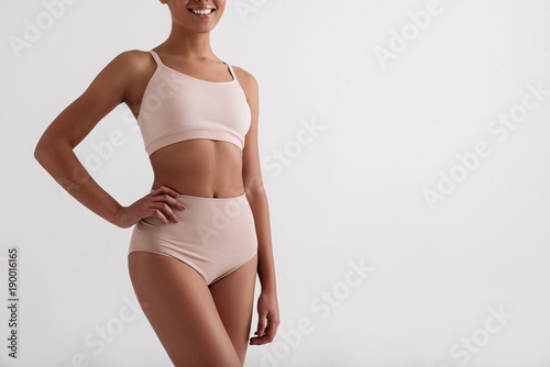 Fototapeta Health concept. Smiling african woman taking care of her slim figure. She is wearing comfortable underclothes. Copy space in right side and Isolated on background obraz na płótnie