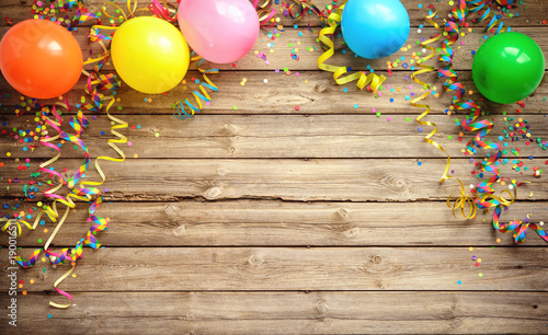 Obraz Colorful carnival or party frame of balloons, streamers and confetti on rustic wooden board - fototapety do salonu