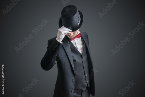 Gallant magician or illusionist in suit is taking off his hat.