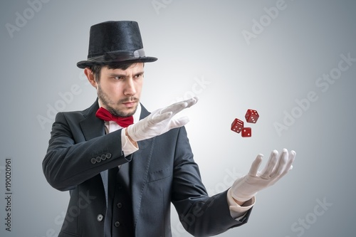 Young illusionist or magician is showing magic trick with levitating dice.