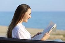 Woman Reading A Newspaper Sitt...