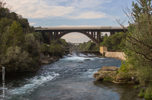 Photo view of dam for hydroelectric power production and highway bridge on the Adda ri