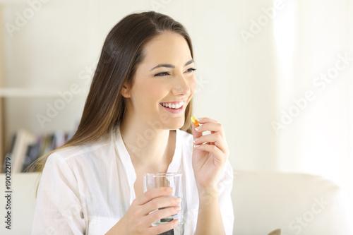Fotografia  Happy woman taking a vitamin yellow pill at home