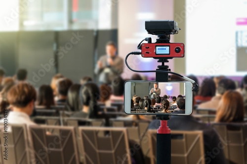 Fototapeta Closeup smart mobile phone taking Live over Speakers on the stage with Rear view of Audience in the conference hall or seminar meeting, technology live streaming and broadcast concept obraz