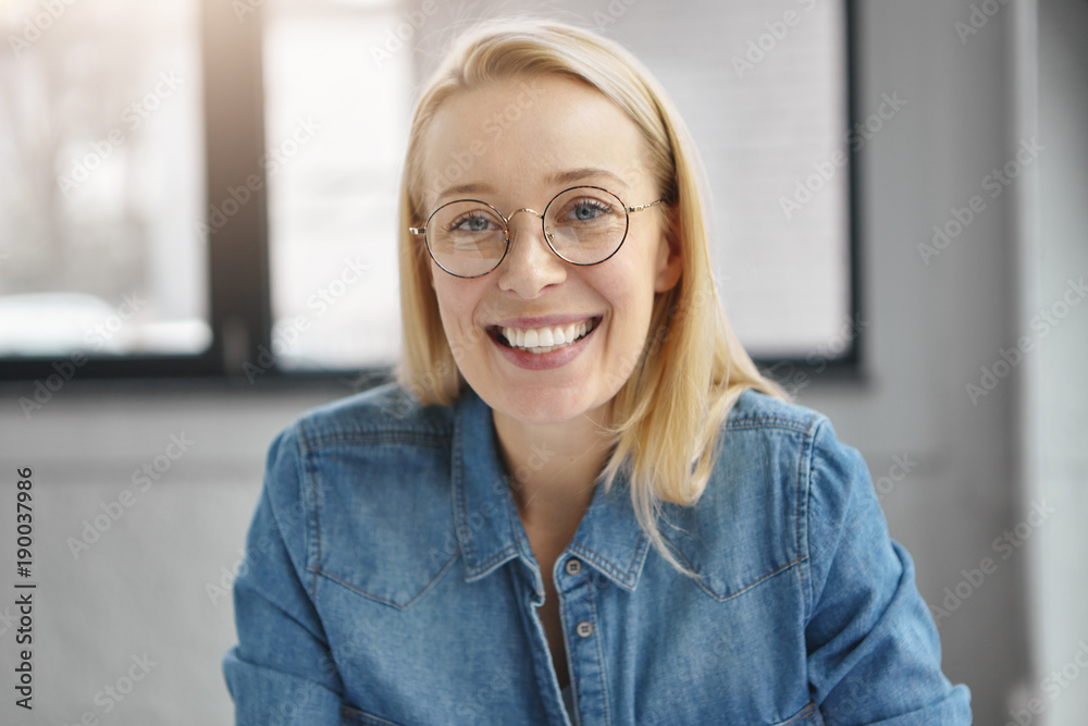 Fototapeta Close up portrait of positive blonde woman in round spectacles, denim jacket, being satisfied with work results, sits in spacious cabinet, expresses positive emotions. People, facial expressions