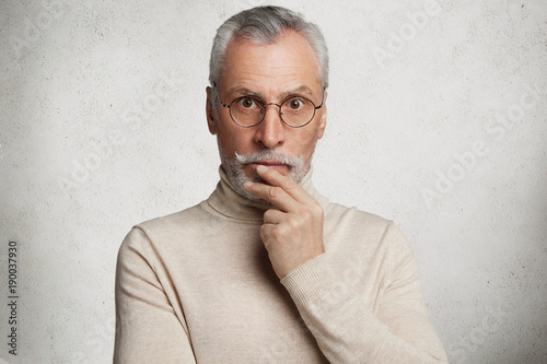 Stupefied senior male in eyewear can`t believe his eyes, sees something unexpected, dressed casually, spends time alone at home, isolated over white concerte wall. People, age and emotions concept