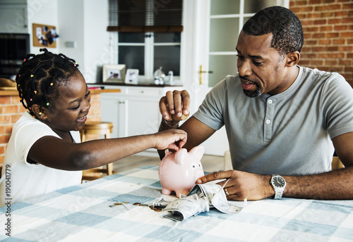 Fotografia, Obraz Dad and daughter saving money to piggy bank