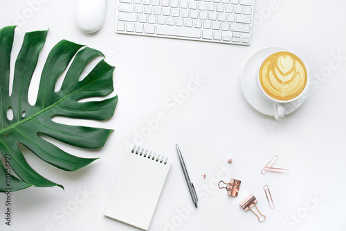 Valokuva  Top view of business desk table with monstera leaves and mock up accessories on white background