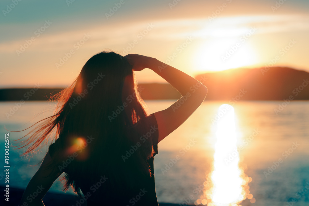 Fototapeta Happy Hopeful Woman Looking at the Sunset by the Sea