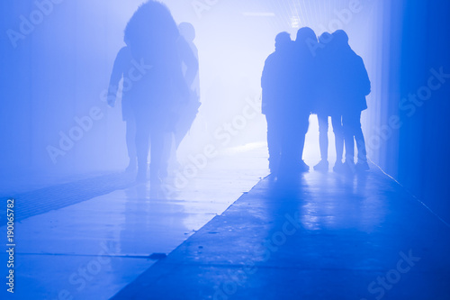 silhouette of people walking in a tunnel in smoke against a background of bright light Tablou Canvas
