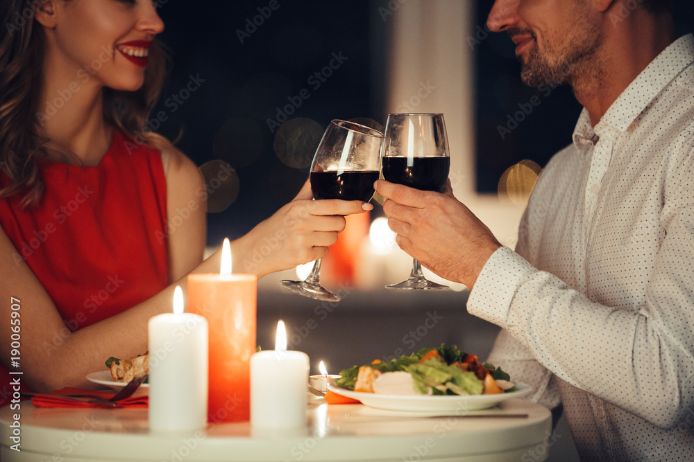 Fototapeta Cropped photo of lovers having romantic dinner at home