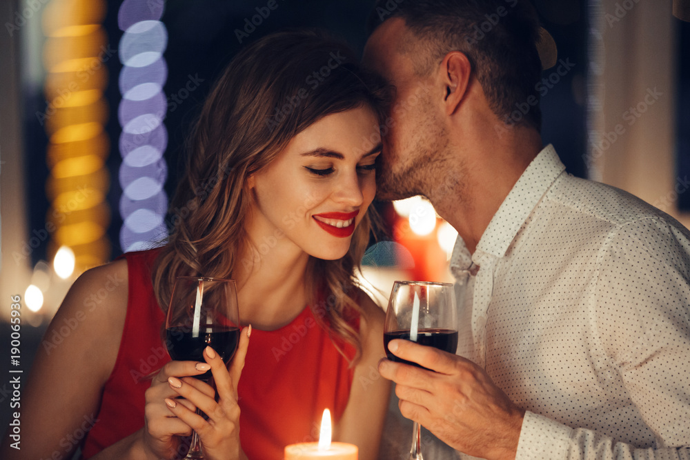Fototapeta Young handsome man whisper to his woman while have romantic dinner