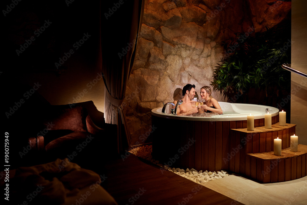 Fototapeta A loving couple with a glass of champagne in a jacuzzi with candles relax.