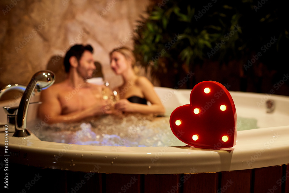 Fototapeta Heart on a background of a romantic couple with champagne in the jacuzzi. Valentines day.