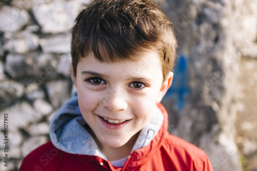 Fotografia  portrait of 9 year old boy with red jacket outside