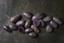 Raw Purple Uncooked Organic Potatoes Named Prunelle, Whole And Slice Over Dark Texture Background. Top View, Copy Space