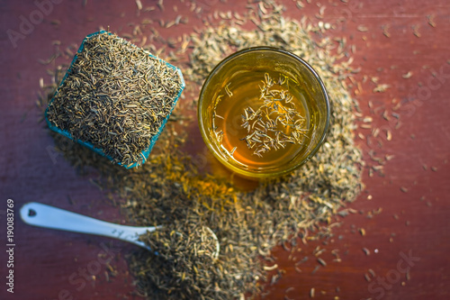 Fototapeta Black cumin seeds,shah jerra,Nigella sativa  and its extracted water in a transparent glass on brown wooden surface.; obraz