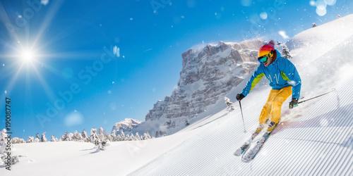 Canvas Prints Winter sports Skier on piste running downhill in beautiful Alpine landscape. Blue sky on background.