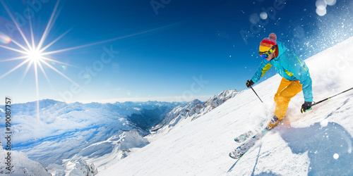 Tuinposter Wintersporten Skier on piste running downhill in beautiful Alpine landscape. Blue sky on background.