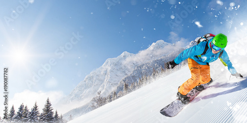 Snowboarder on piste running downhill in beautiful Alpine landscape. Blue sky on background.