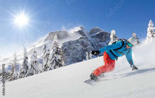 obraz dibond Young man snowboarder running downhill in Alps