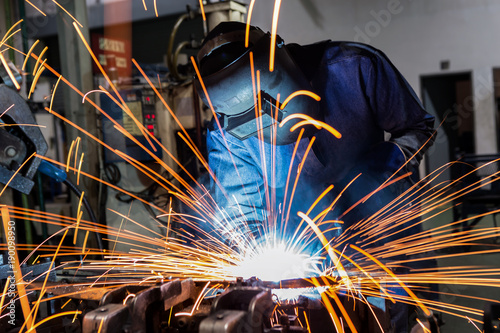 Staande foto Industrial geb. Industrial worker is welding car in factory
