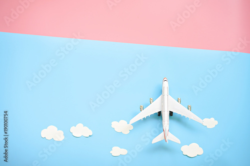 Fotografia  Flat lay design of travel concept with plane and cloud on blue and pink background with copy space