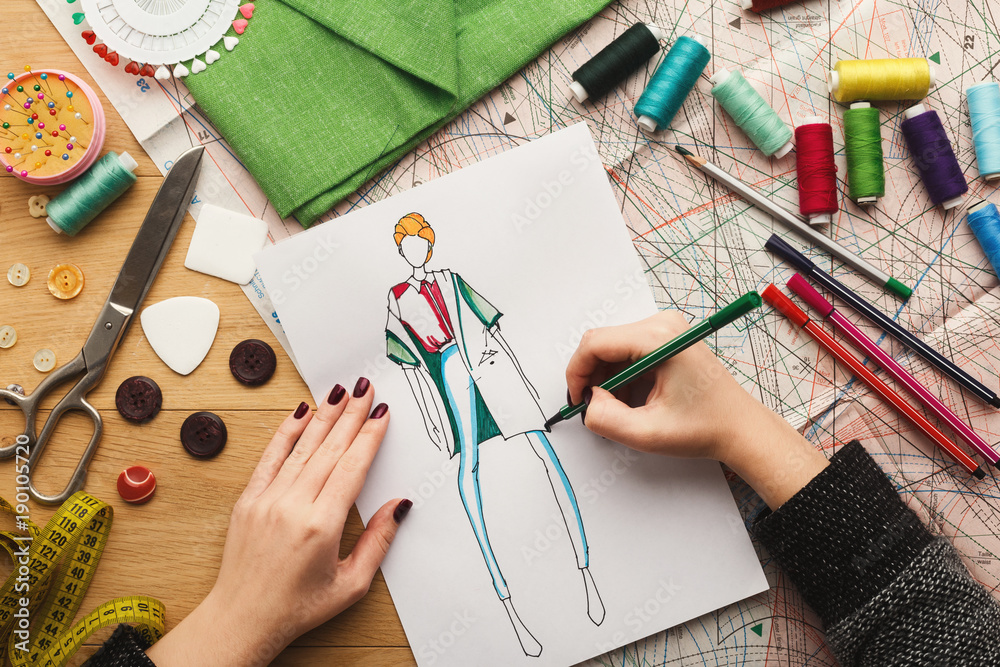 Fototapeta Top view on woman designer drawing clothes sketches