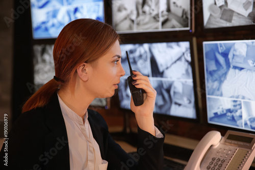 Foto  Female security guard using radio transmitter in surveillance room