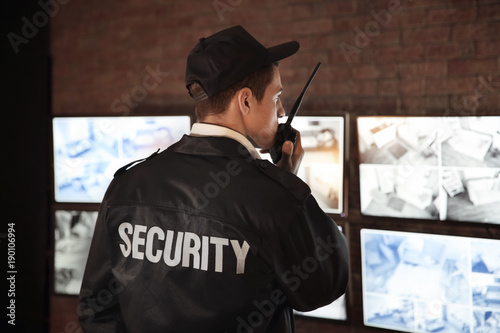 Foto  Male security guard using radio transmitter in surveillance room