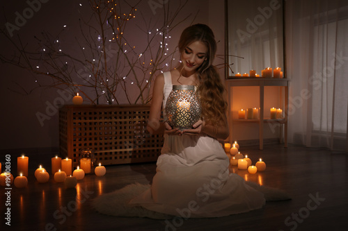 Foto op Plexiglas Wand Beautiful young woman holding candle at home