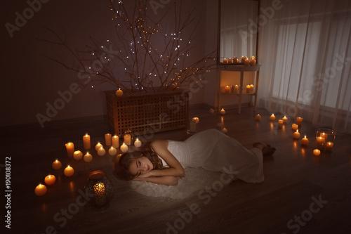 Foto op Plexiglas Wand Woman lying near burning candles on floor at home