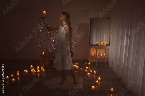 Foto op Plexiglas Wand Beautiful young woman holding candle in dark room