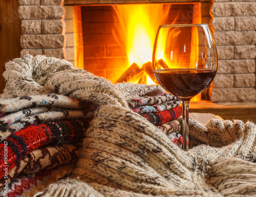 Glass of red wine; and wool; things near cozy fireplace. Canvas Print