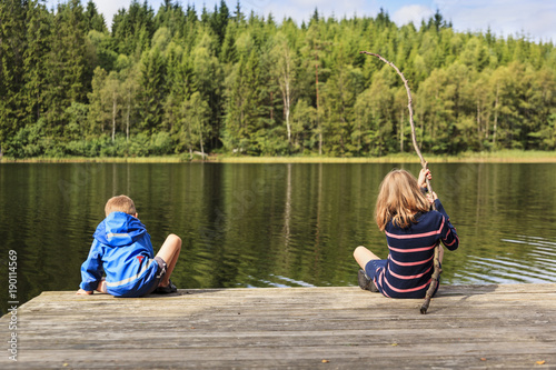 Fotografie, Obraz  Two children using a homemade fishing rod fishing from a jetty by a lake set in an idyllic Swedish summer forest landscape