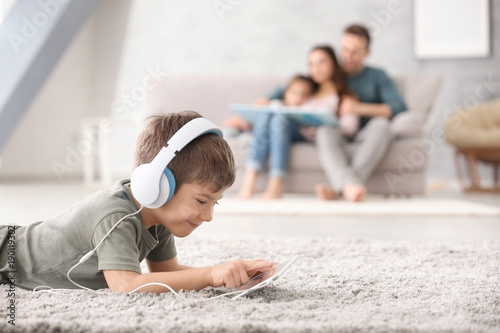 Cute little boy with tablet computer at home Canvas Print
