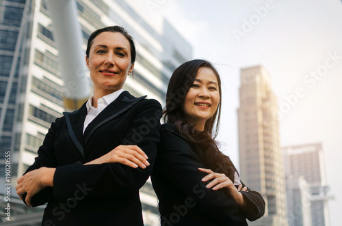 Two Smiling Business Asian And Caucasian Woman In Formally Dressed