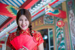 Portrait of beautiful asian woman in Cheongsam dress with Red envelope in hand,Thailand people,Happy Chinese new year concept