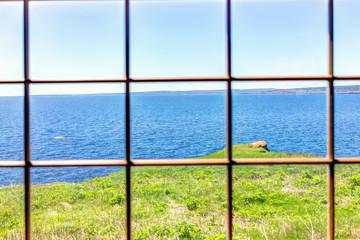 Patrząc przez stare okno domu z klifu i widokiem na ocean w Bonaventure Island, Quebec, Kanada