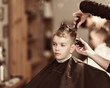 Handsome boy getting his hair and beard cut at barber shop