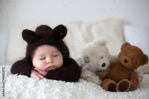 Fototapeta Sweet little baby boy, dressed in handmade knitted brown soft teddy bear overall, sleeping cozy obraz na płótnie