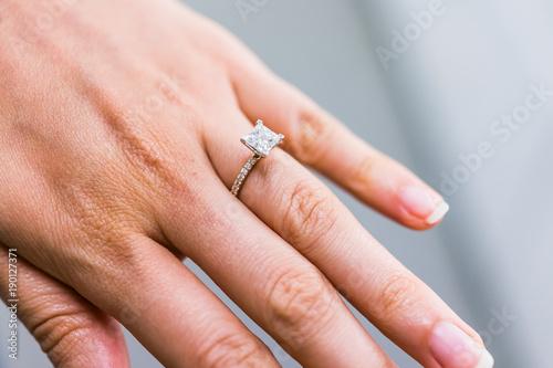 Fotografie, Obraz  Macro closeup of princess cut diamond engagement ring on woman's female hand sho