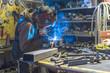 Young attractive worker Metal shop welding girding in progress