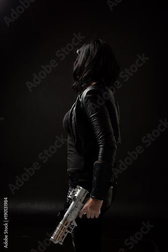 Fotografía  portrait of black haired girl wearing leather clothes, moody lighting on black background