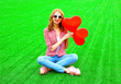 canvas print picture - Young smiling woman with red an air balloon in the shape of a heart sits on the grass