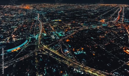 Aerial view of a massive highway in Los Angeles, CA at night with young woman holding out a smartphone in her hand