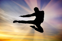 Silhouette Of A Man Flying Kic...